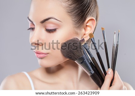 Stock Photo Beauty girl with makeup brushes. Perfect smooth skin.Applying makeup.Beautiful young woman holding different make up brushes
