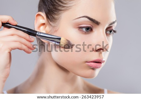 Beauty girl with makeup brushes. Perfect smooth skin.Applying makeup.Beautiful young woman holding different make up brushes