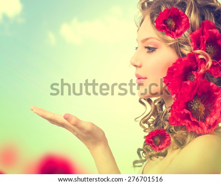 Stock Photo Beauty girl with red poppy flowers hairstyle and open hands. Blowing flower. Hairstyle with flowers. Fantasy girl portrait over blue sky outdoor. Summer fairy portrait. Long permed hair