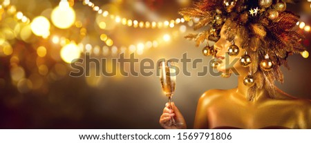 Beauty Glamour Golden Christmas Woman celebrating with champagne, wearing wreath decorated with baubles. Party, drinking sparkling wine, glowing holiday background. Xmas, New Year Holiday celebration