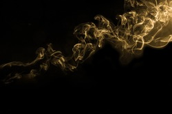 Beauty gold smoke on dark background,movement golden of fire flame smoke, Abstract and texture of amazing magic gold smoke on black background