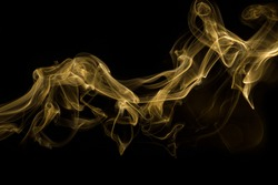 Beauty gold smoke on dark background, movement golden of smoke on fire flame, Abstract and texture of amazing magic golden smoke on black background