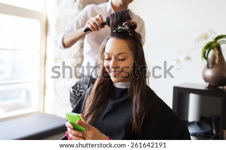 beauty, hairstyle and people concept - happy young woman with smartphone and hairdresser making hair styling at salon #261642191