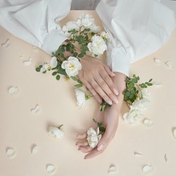 Beauty hands woman with rose flowers are on the table. Natural cosmetic for hand skin care. Fashion makeup