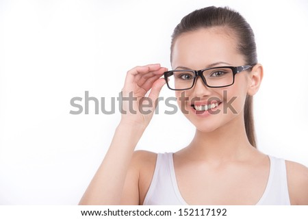 Beauty in glasses. Beautiful young woman in glasses looking at camera and smiling while isolated on white