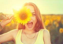 Beauty joyful teenage girl with sunflower enjoying nature and laughing on summer sunflower field. Sunflare, sunbeams, glow sun. Backlit.