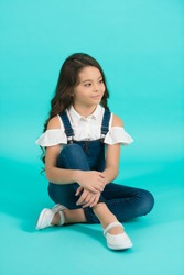 Beauty, look, hairstyle. Girl smile with long brunette hair on blue background. Child model in jeans overall sit on floor. Fashion, style concept. Childhood, preteen, youth, punchy pastel