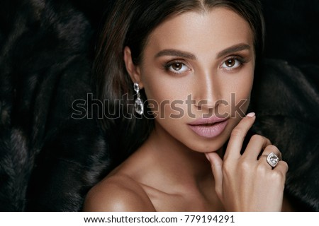 Beauty Makeup. Gorgeous Woman Face With Jewelry. Sexy Young Female In Luxury Black Fur Coat With Beautiful Facial Makeup Wearing Gold Diamond Earrings And Ring. Fashion Look. High Quality Image.