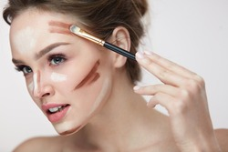 Beauty Makeup. Portrait Of Beautiful Young Female With Smooth Skin And Fresh Makeup And Hands With Brush Applying Make-Up Product, Conturing And Highlighting Lines On Sexy Woman Face. High Resolution