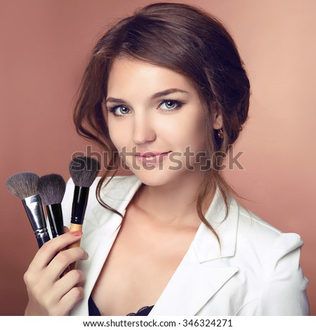 Beauty makeup professional stylist. Makeup artist holding brushes. Attractive Woman face Portrait.  Isolated on studio background.
