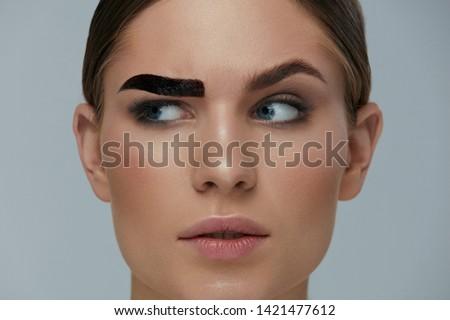 Beauty makeup. Woman coloring eyebrow with gel tint closeup. Girl model setting liquid peel-off brow gel on eyebrow