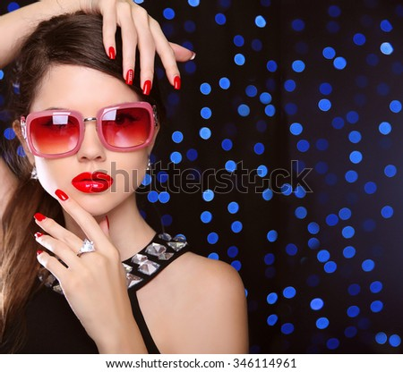 Beauty. manicured nails. Fashion model girl in sunglasses with bright makeup, luxurious jewelry over  on blue lights background.