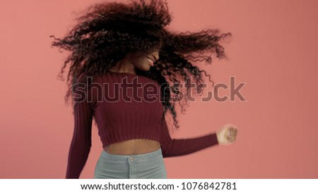 Beauty mixed race african american woman with hair blowed in air smiling at camera dancing Soft focus in movement