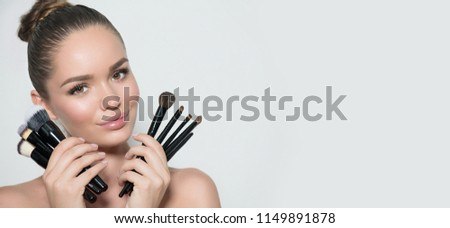 Beauty model girl, makeup artist holding set of make up brushes and smiling. Beautiful brunette young woman with perfect skin and nude make-up. Perfect skin closeup. Face contouring makeup