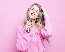 Beauty model girl singer with a microphone over pink background