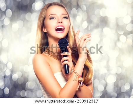 Beauty model girl singer with a microphone singing and dancing over holiday glowing background. Karaoke party singer. Disco party. Celebration