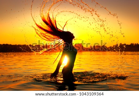 Beauty Model Girl Splashing Water with her Hair. Model girl silhouette over sunset sky. Swimming and splashing on summer beach over sunset. Beautiful Woman in Water