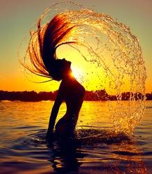 Beauty Model Girl Splashing Water with her Hair. Teen girl Swimming and splashing on summer beach over sunset. Beautiful Woman in Water