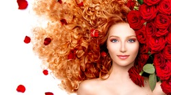 Beauty model girl with long curly red hair and beautiful red roses hairstyle. Fashion woman with Wavy healthy hair isolated on white background. Permed hair