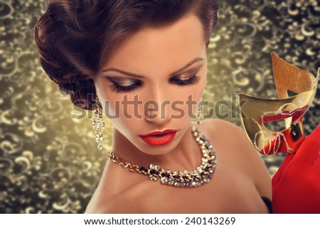 Stock Photo Beauty model woman wearing venetian masquerade carnival mask at party, over holiday dark background. Christmas and New Year celebration. Sexy girl with holiday makeup and manicure. Red lips