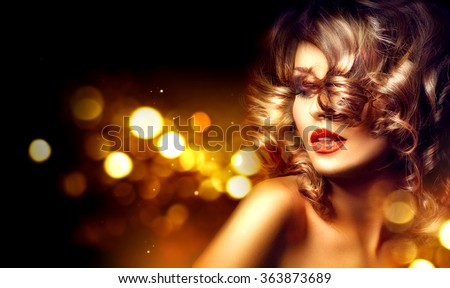 Beauty model woman with beautiful make up and curly hair style over holiday dark background with magic glow. Holiday celebration. Brunette Glamour lady with perfect make up and hairstyle