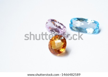 Beauty of Colorful loose gemstones on white background. Fancy Faceted Round-shape Orange color Citrine Quartz, Faceted Long Oval-shape Pale Pink Kunzite and Bright Faceted Cushion- shape Blue Topaz.