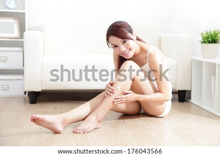 Beauty of young pretty woman with perfect shape and applying cream on her attractive legs indoors at home, asian beauty