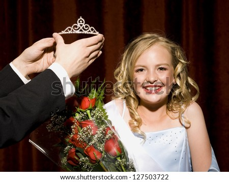 Beauty pageant winner smiling, holding roses and getting her crown