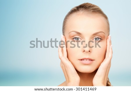 beauty, people and body care concept - beautiful young woman touching her face over blue background #301411469