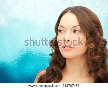 beauty, people and health concept - beautiful young woman face over ripple blue water background