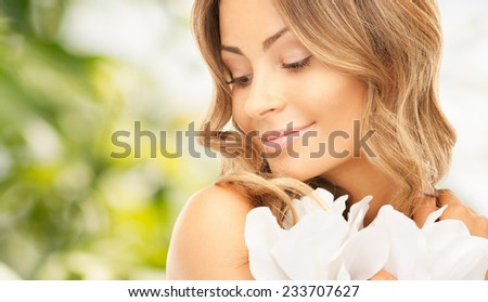 beauty, people and health concept - beautiful young woman with flowers and bare shoulders over green background