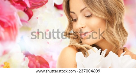 beauty, people and health concept - beautiful young woman with flowers and bare shoulders over pink floral background