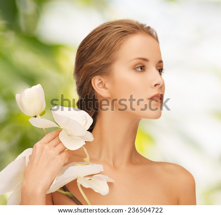 beauty, people and health concept - beautiful young woman with orchid flowers and bare shoulders over green background