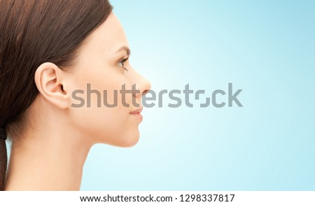 beauty, people and plastic surgery concept - beautiful young woman face over blue background