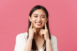 Beauty, people emotions and summer leisure concept. Close-up of funny and cute asian woman with kawaii dimples, touching cheeks and smiling happy, standing pink background