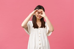 Beauty, people emotions and summer leisure concept. Lovely, romantic shy asian girl in white dress confess sympathy or love, like someone, showing heart sign and smiling over pink background