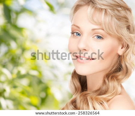 beauty, people, hair care and health concept - beautiful young woman face with long wavy hair over green background