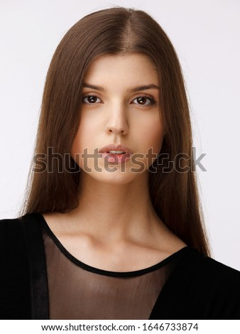 Beauty people portrait. Girl of a natural skin, wear in black dress, looking at camera, over white background.