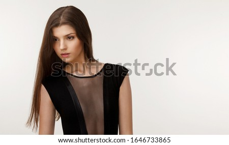 Beauty people portrait, girl with clear skin and long hair, in black dress, looking at away, over white background.