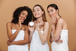 Beauty photo of three smilng multiracial women with different types of skin: caucasian, african american and asian girls, applying face cream together isolated over beige background