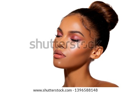 Beauty Porter young Dark Skinned Girl with perfect skin and Makeup. Bridal makeup delicate Pink tones, Wet make-up, shine. Sexy lips. Hair gathered in the bun on his head. Vivid Pink makeup. Beauty.