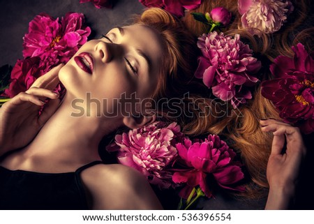 Beauty portrait. Beautiful blonde woman with sensual maroon lips lying among peony flowers. Cosmetics, make-up. Perfumery.
