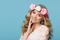 Beauty portrait. Beautiful blonde woman with wreath of flowers. Looking at camera. Touching hair. Isolated on blue background. Youth, happiness concept