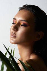 Beauty portrait for tanned girl with make-up and wet hair in palm leav
