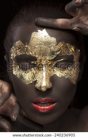 Beauty portrait of a brown-skinned girl with golden makeup of foil closed eyes and red lips.