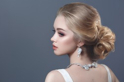 Beauty portrait of a cute blonde bride with beautiful hairstyle isolated on gray background.