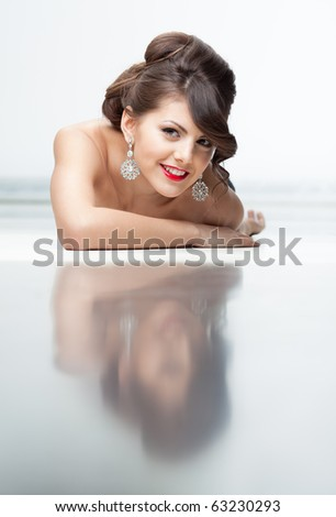 Beauty portrait of a cute girl laying on the floor smiling and her reflexion