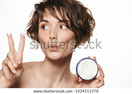 Beauty portrait of a lovely young topless woman with short brunette hair standing isolated over white background, applying face cream, showing container, showing fingers