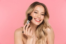 Beauty portrait of a lovely young woman with long blonde hair standing isolated over pink background, holding makeup brush