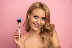 Beauty portrait of a lovely young woman with long blonde hair standing isolated over pink background, holding makeup brush.